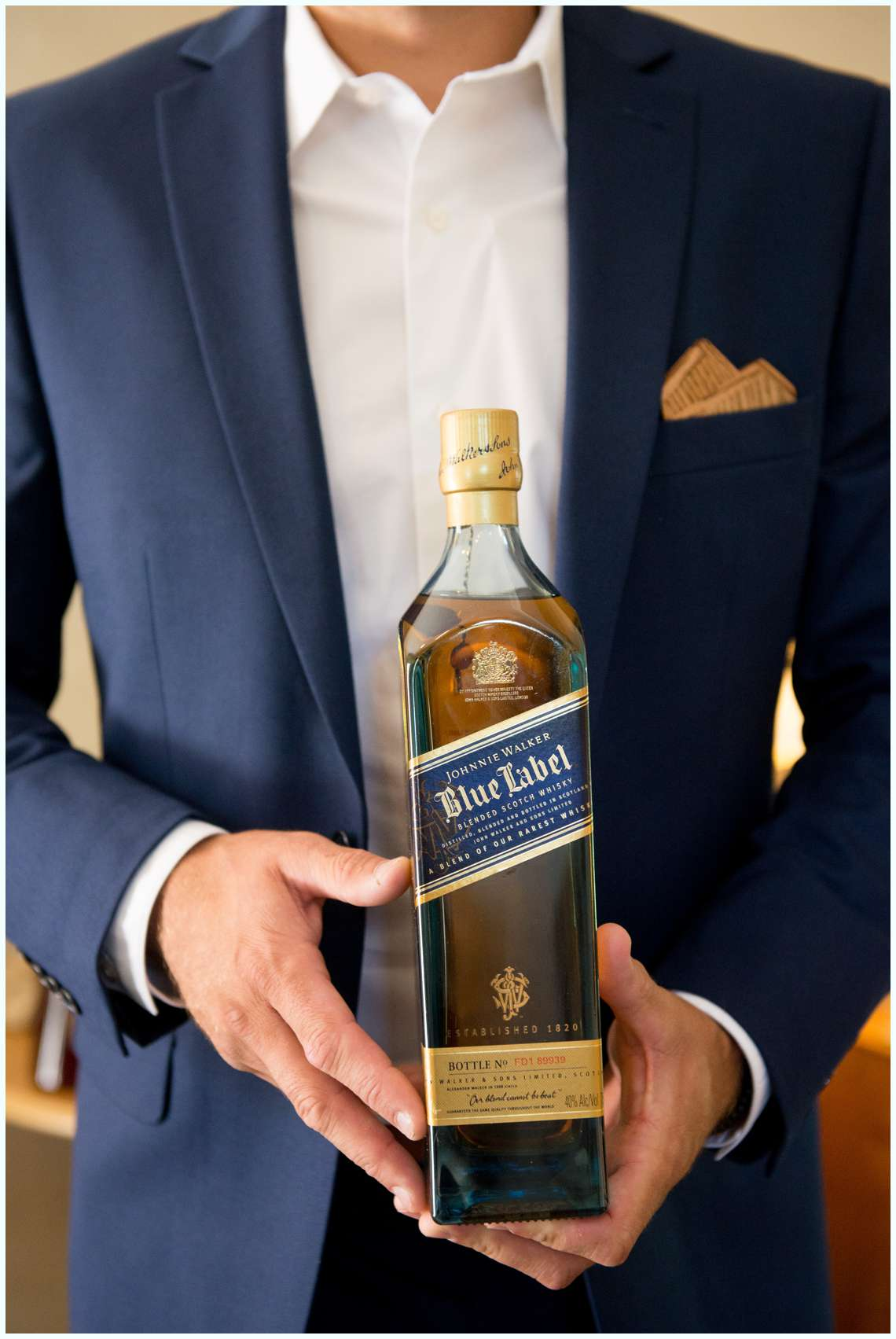 Groom holding bottle of whisky on wedding day with navy blue suit in New Hampshire Johnnie Walker blue label