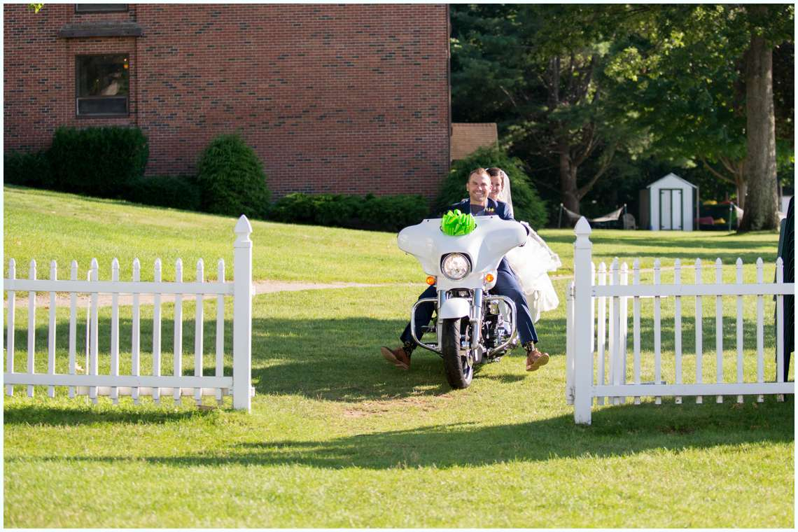 the bride and groom riding in to wedding reception on motorcycle