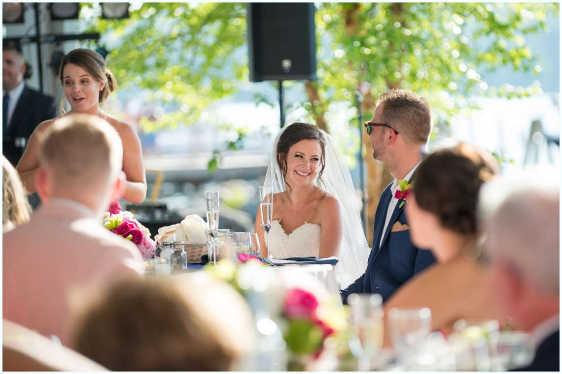 bride and groom smiling while maid of honor speaks at wedding reception