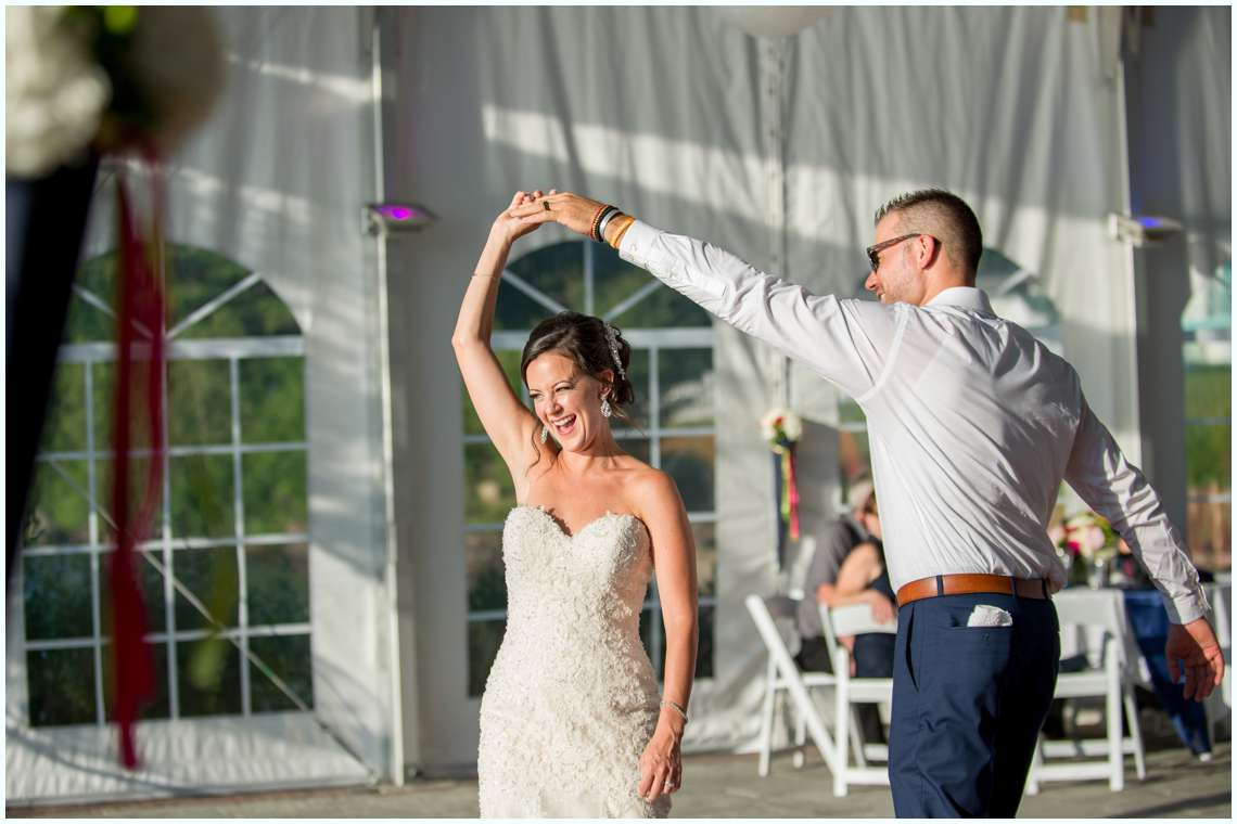 Bride spinning while dancing at wedding reception with groom