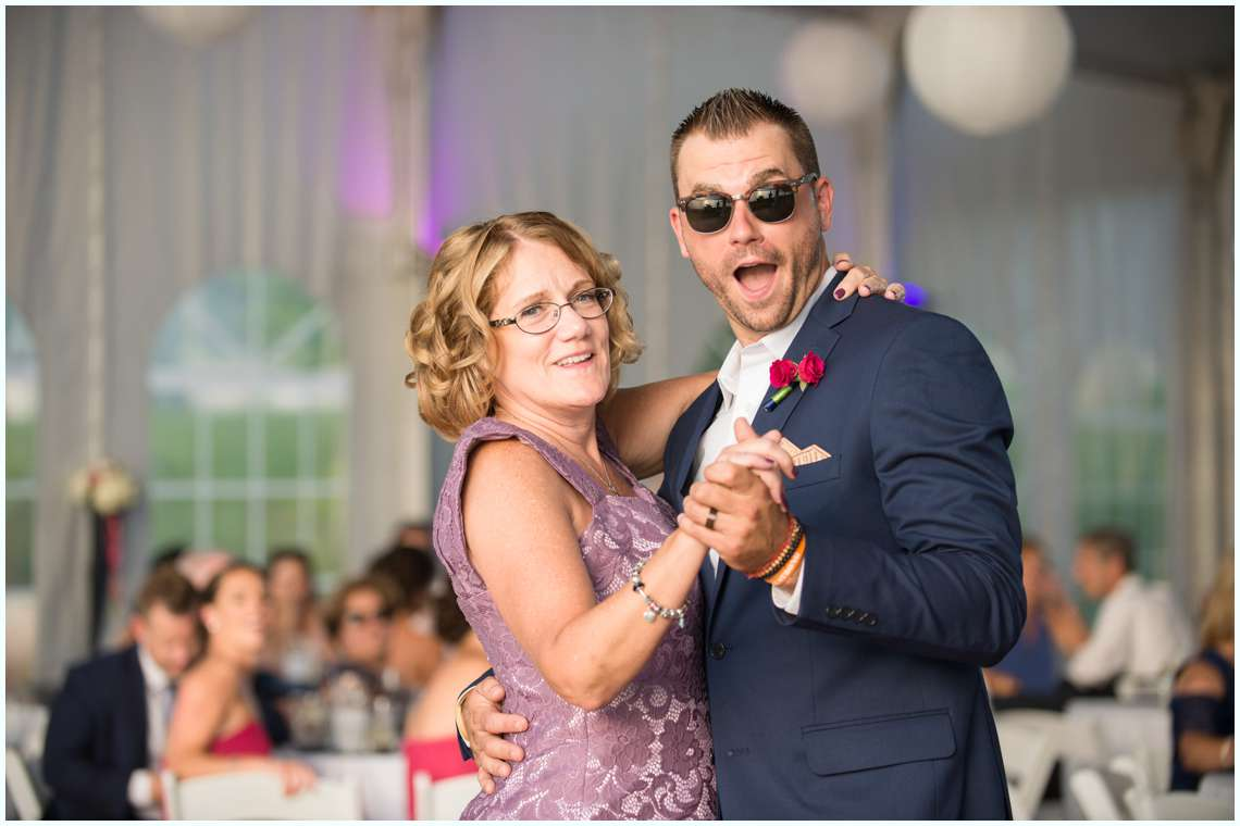 Groom with mom dancing under a white tent for wedding reception