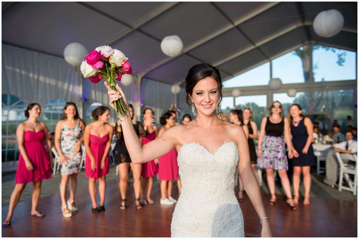 bride tossing bridal bouquet at wedding in tent
