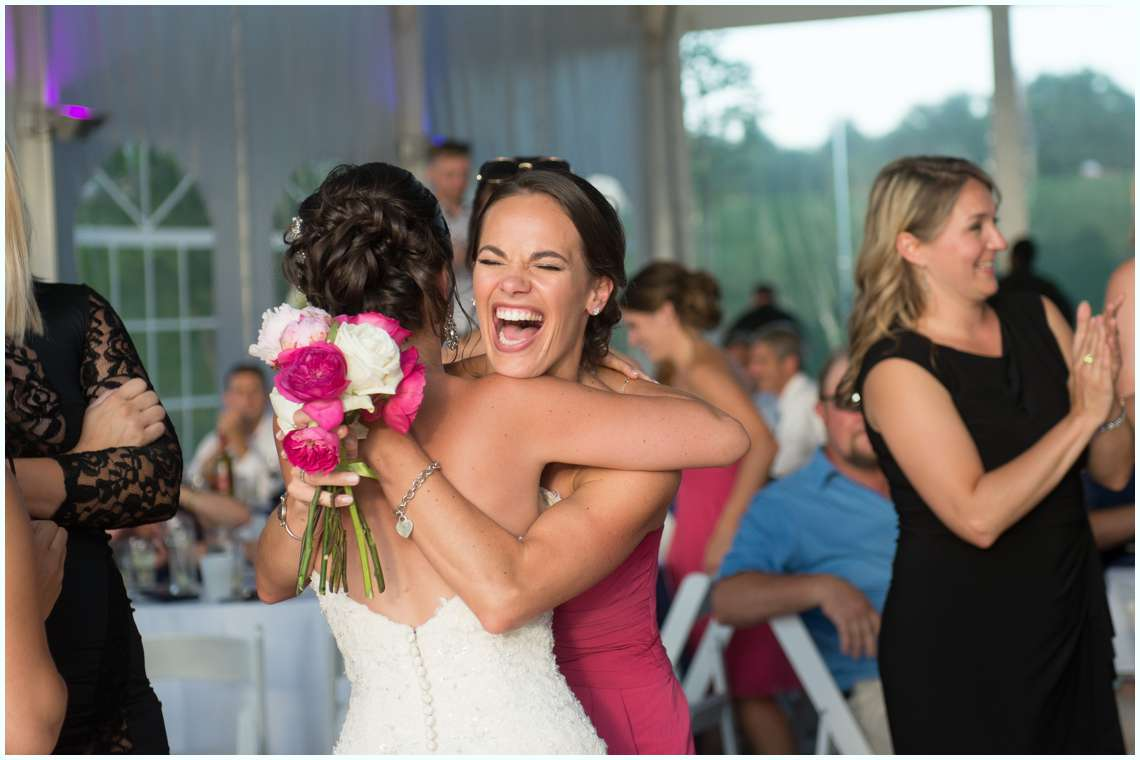 bridesmaid smiling with excitement with bride at wedding reception