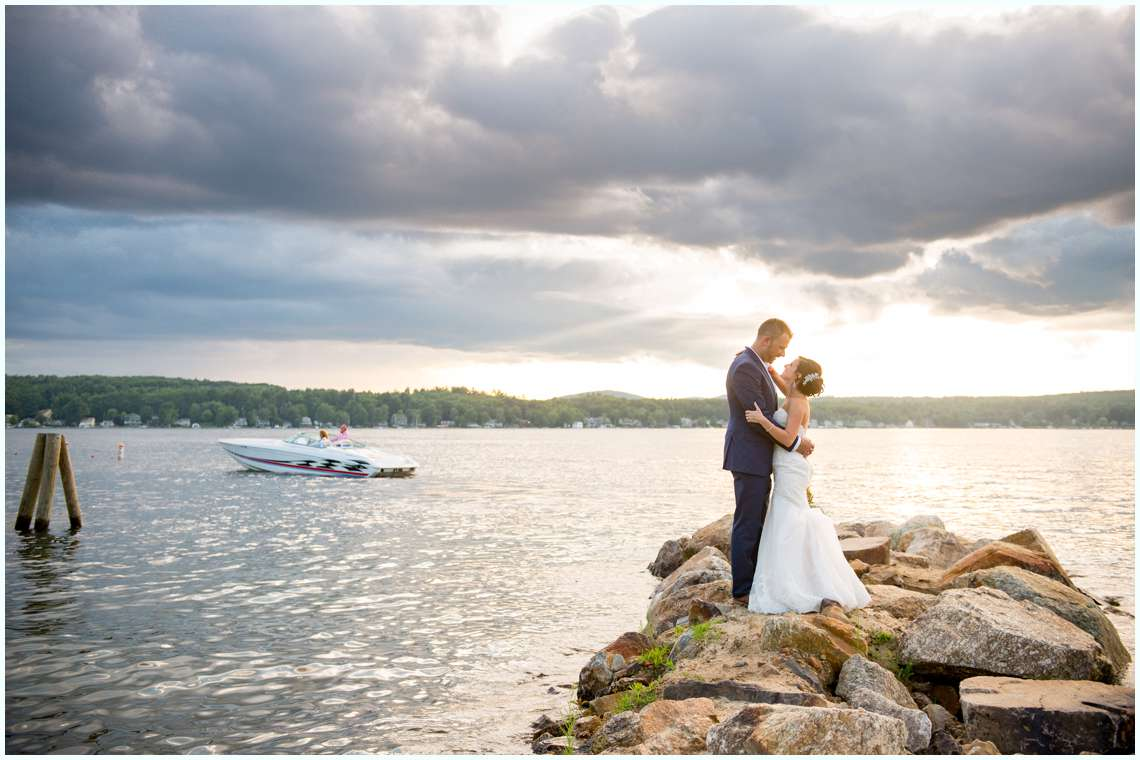 bride and groom standing by lake during sunset with boats
