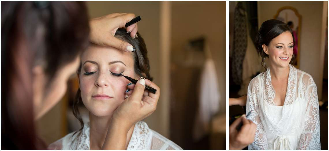 Bride getting makeup done in lace robe on wedding day
