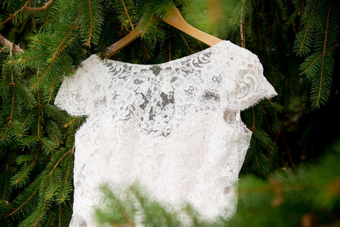 Lace wedding dress hanging on a pine tree for camp wedding
