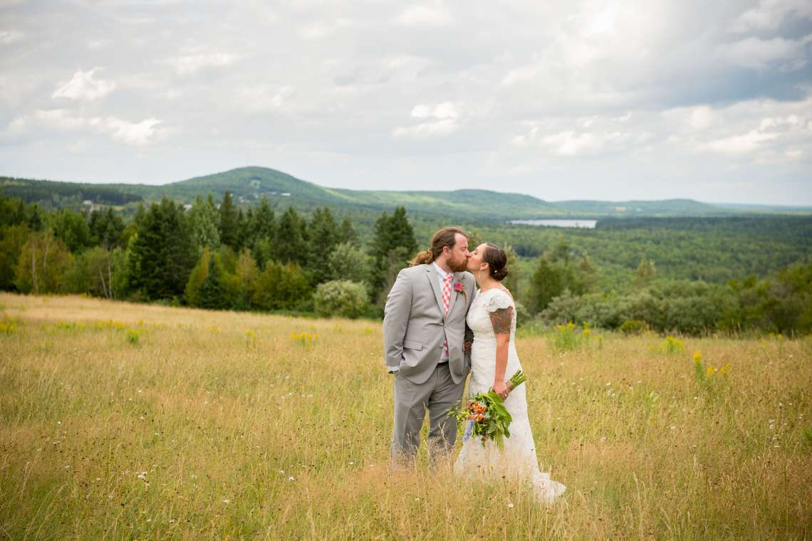 passionate photo of bride and groom in field on wedding day