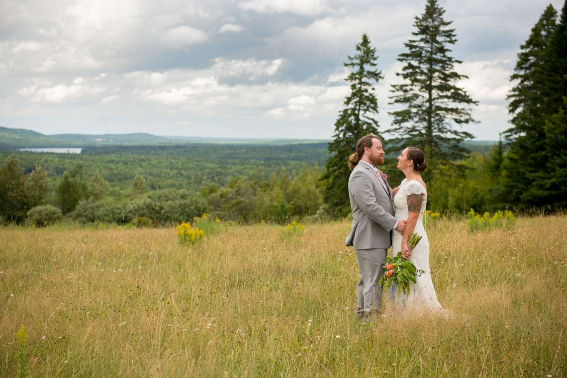 Excited couple on wedding day in a Maine field with mountains