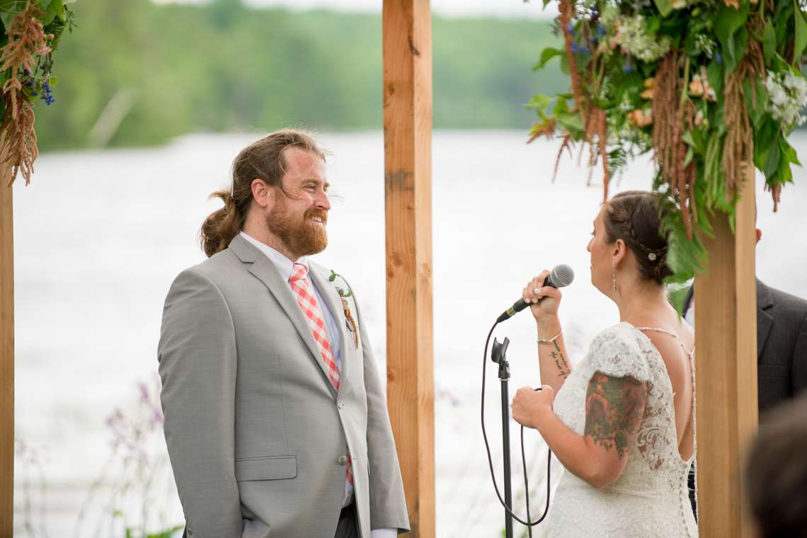 Groom smiling at bride during wedding ceremony at a lake