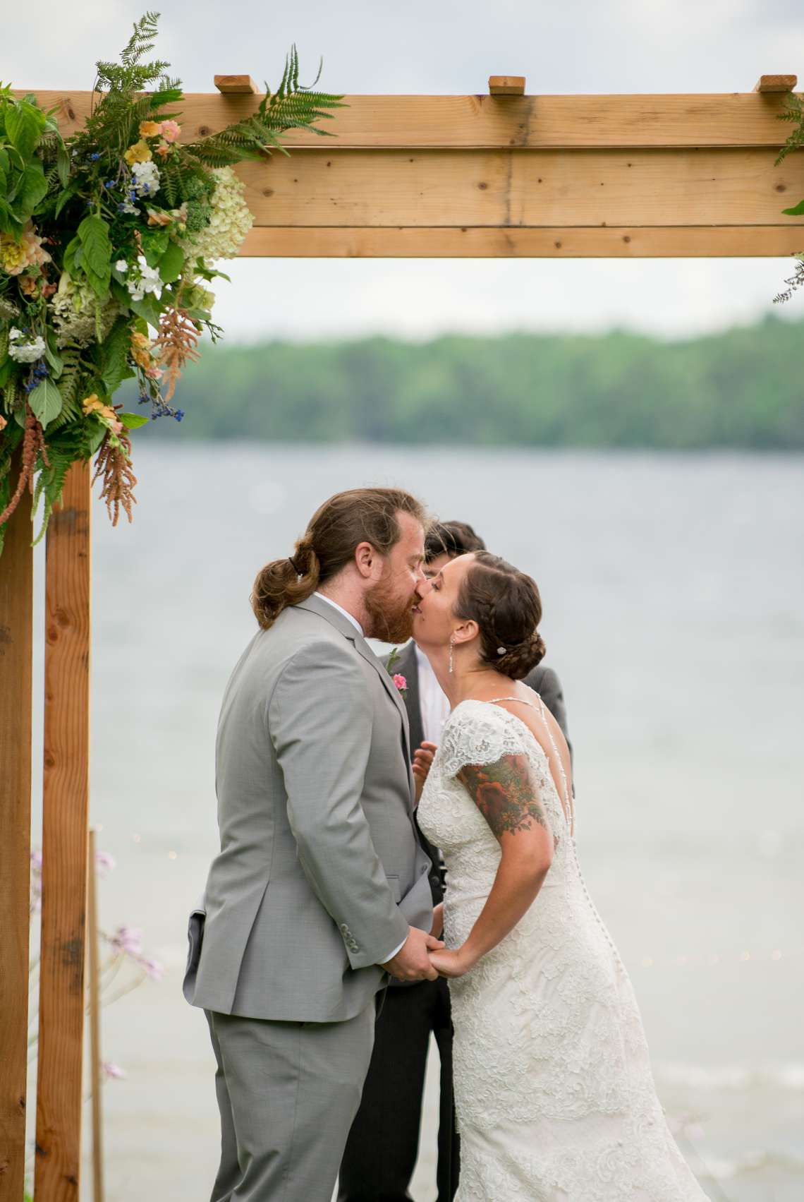 bride and groom kissing under an arbor