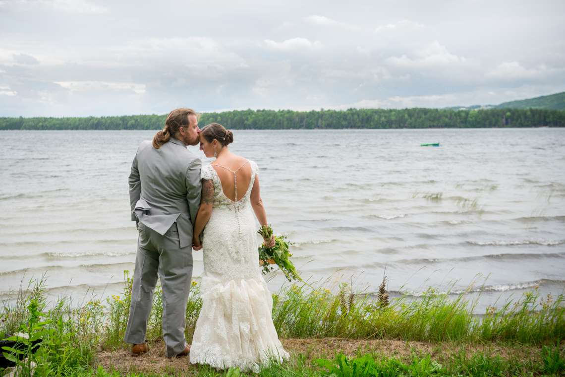 affectionate couple standing next to lake on wedding day