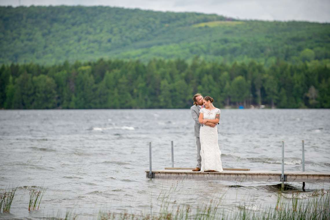bride and groom kissing on a dock in Maine