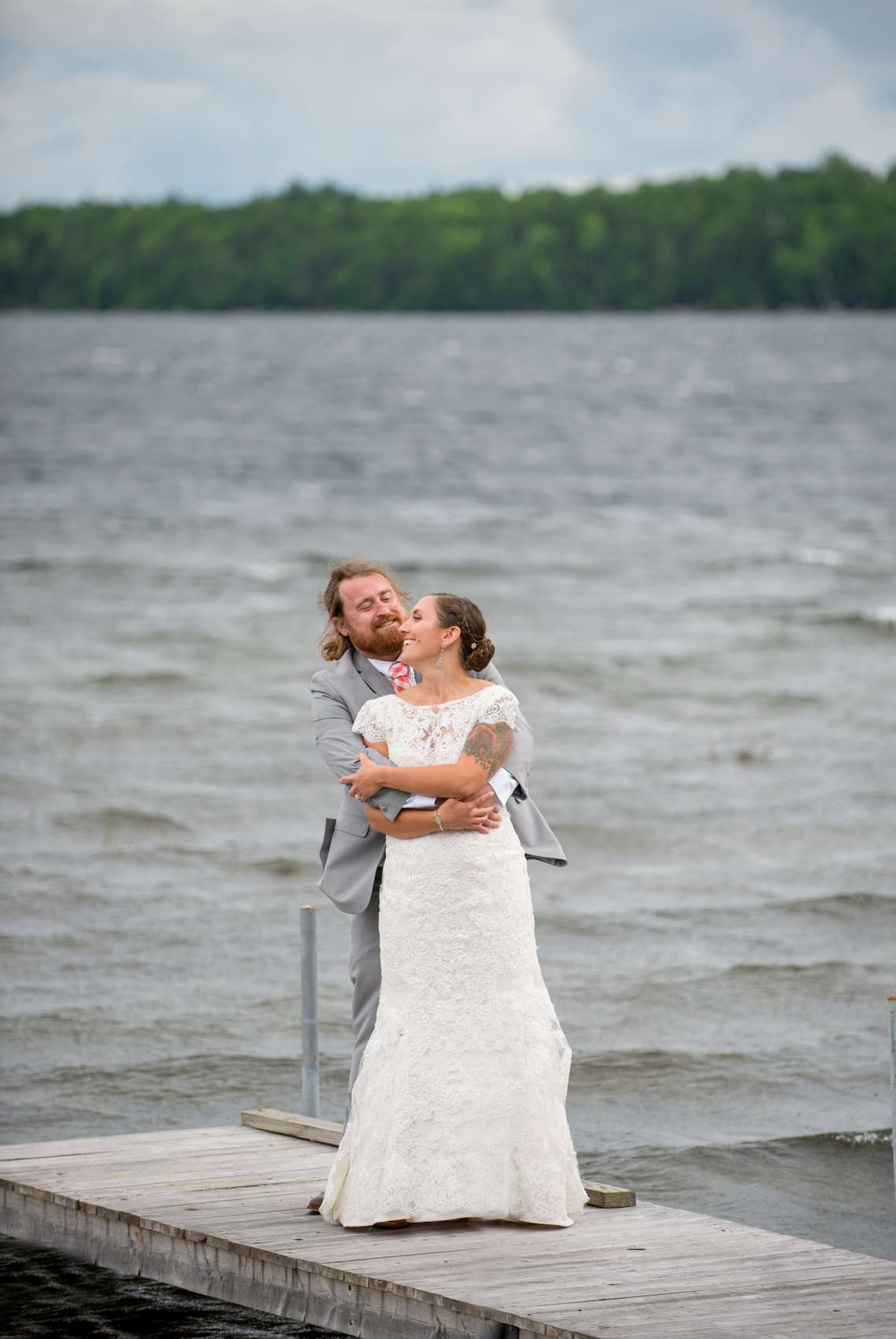 bride and groom on a dock at a camp wedding
