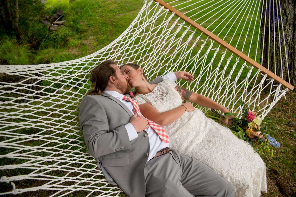 bride and groom kissing in a hammock at a camp wedding