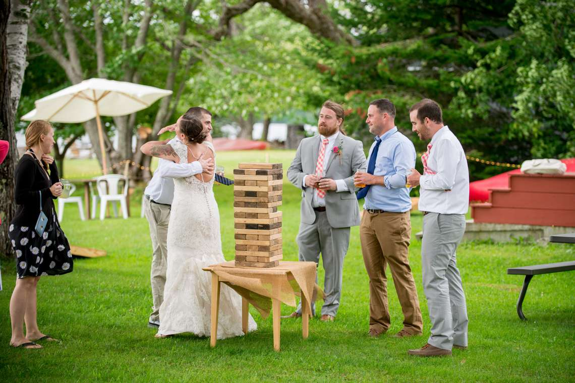 happy couple celebrating with friends paying lawn games at a lakeside wedding