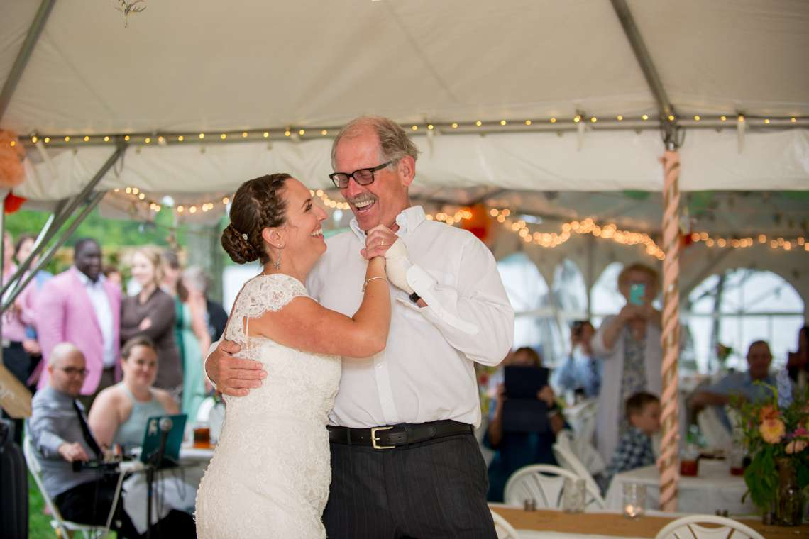 happy bride dancing with dad while laughing