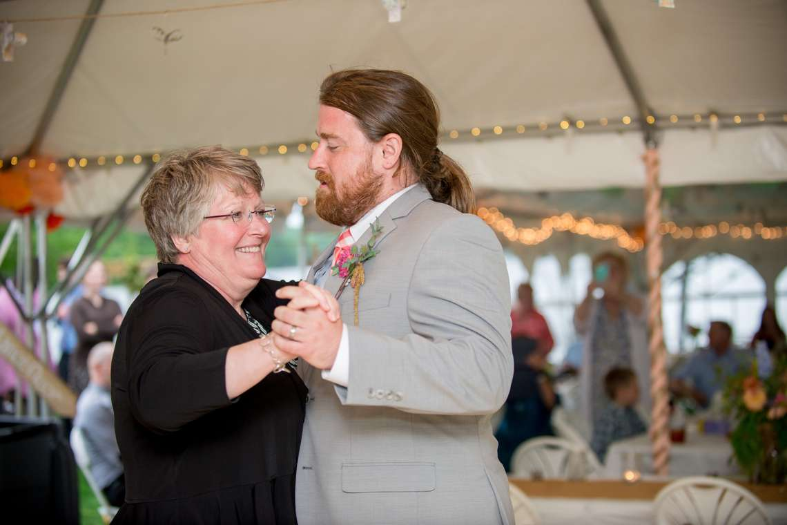 happy groom and mother of the groom dancing at wedding reception