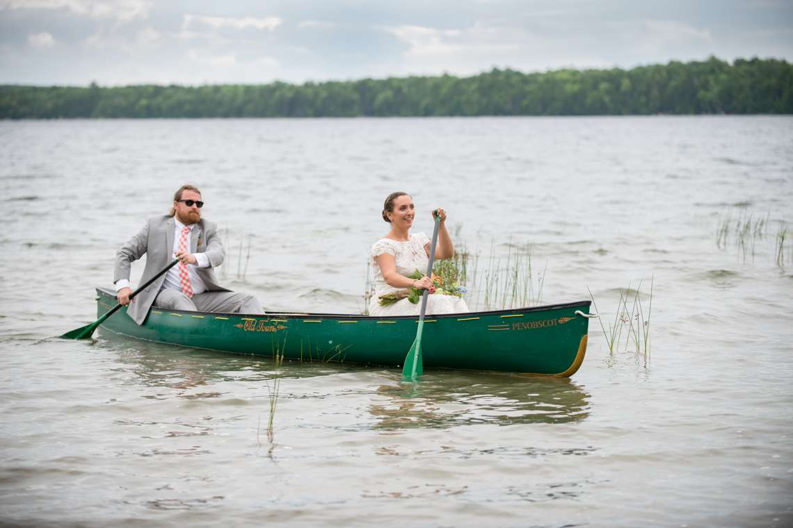 bride and groom in a canoe on wedding day in Maine