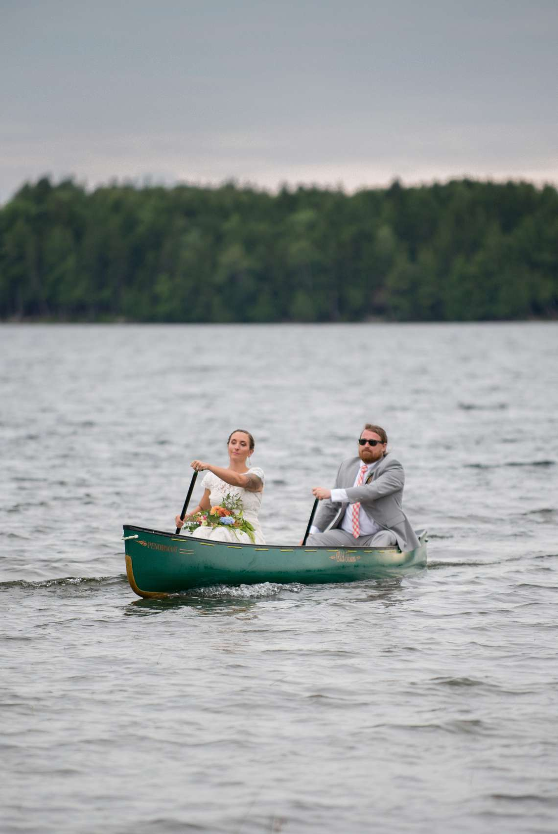 Adventurous bride and groom paddling a canoe on wedding day