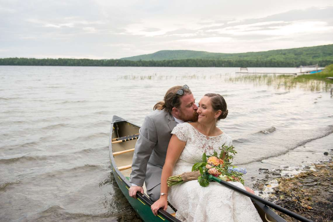 Maine Camp Wedding with bride and groom kissing in a canoe on a lake