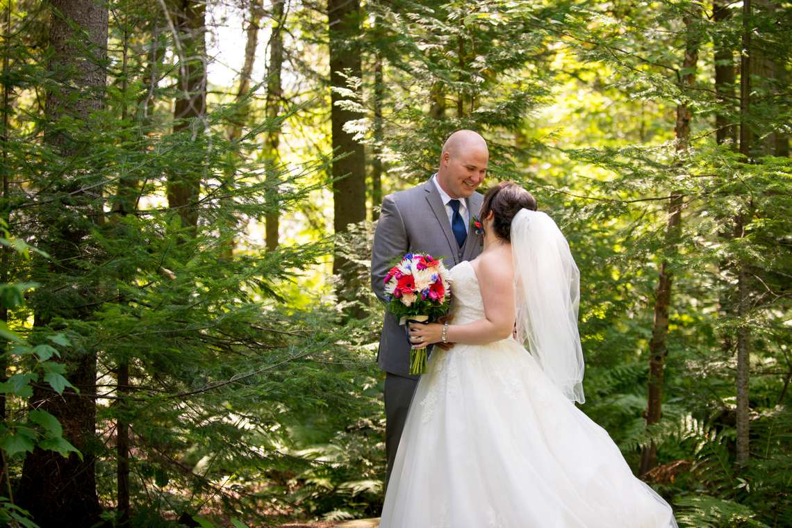 groom smiling at bride in the woods for first look