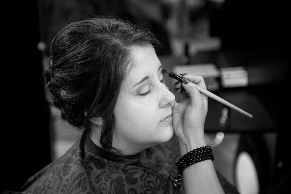 bride getting make up done on wedding day