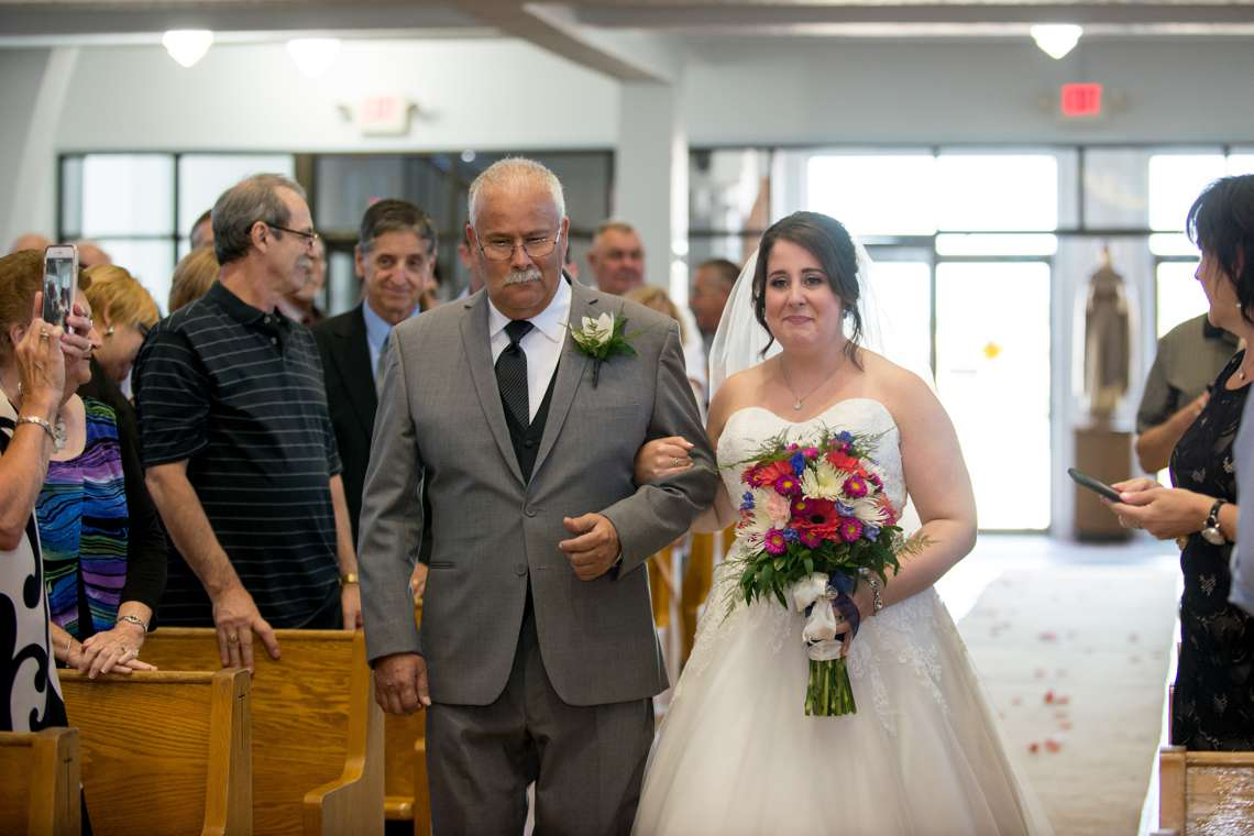 Emotional bride walking down the aisle in church ceremony