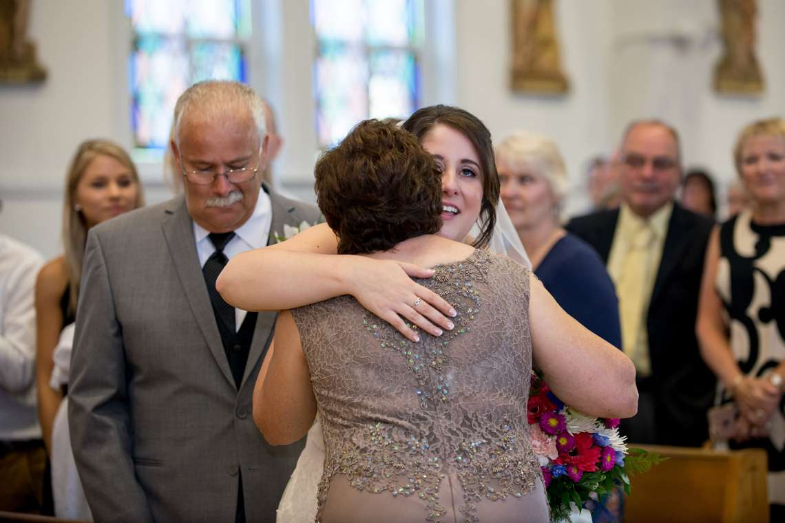 Bride hugging mom during wedding ceremony