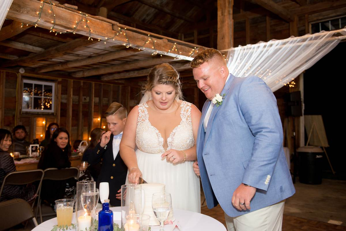 excited and happy couple cutting wedding cake in barn