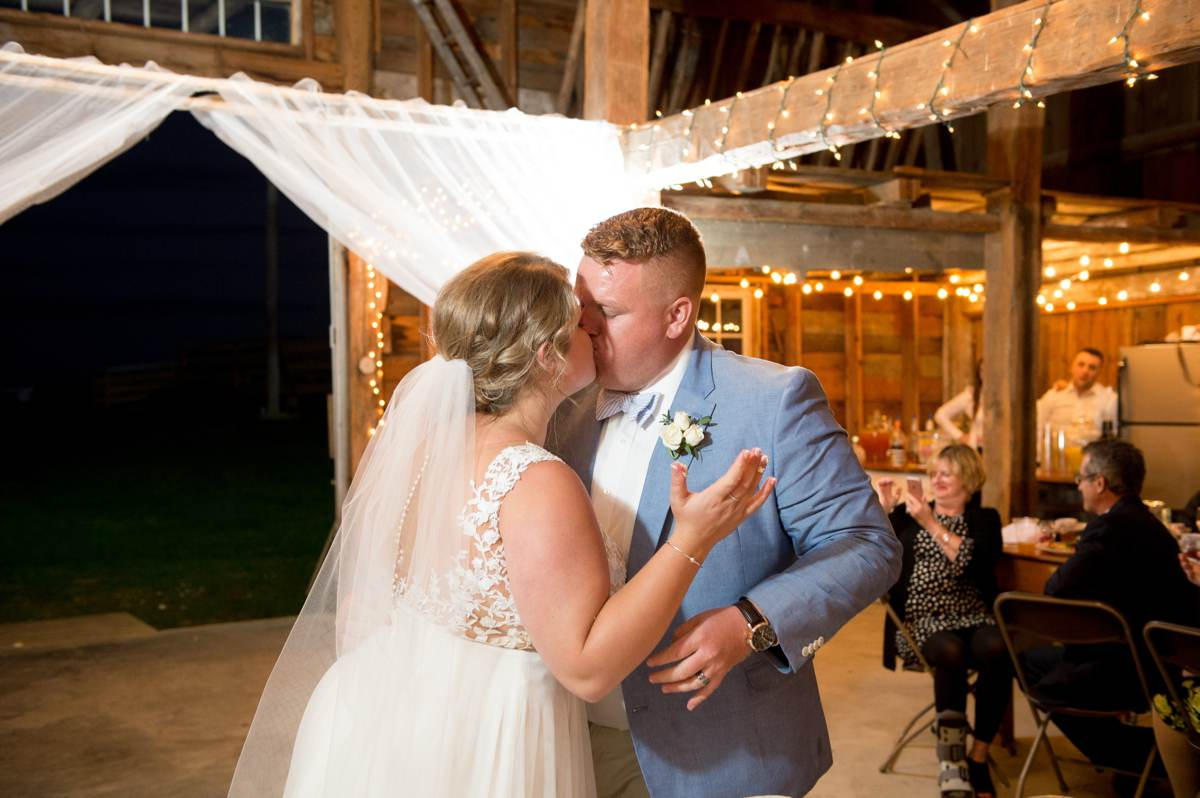 bride and groom kissing after cutting cake at Vista of Maine Vineyard & Cidery Barn reception