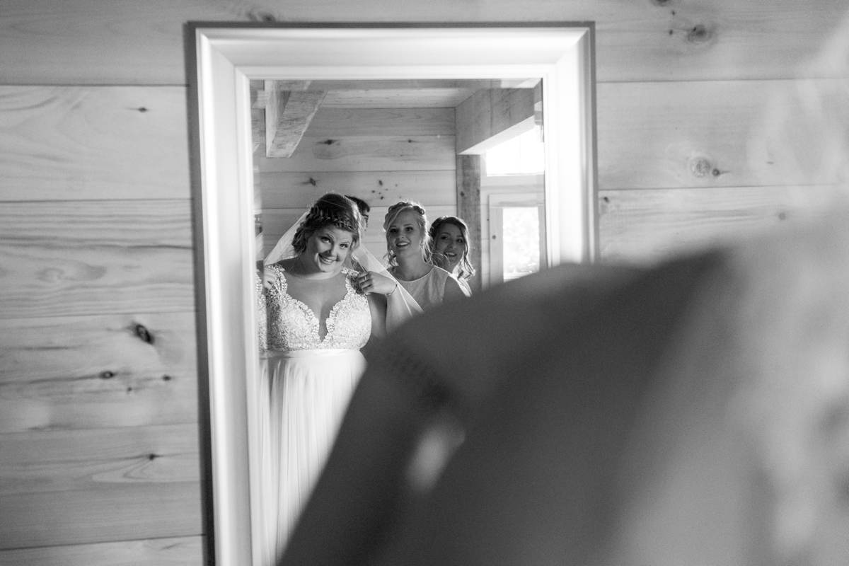 bride looking in mirror on wedding day in Maine