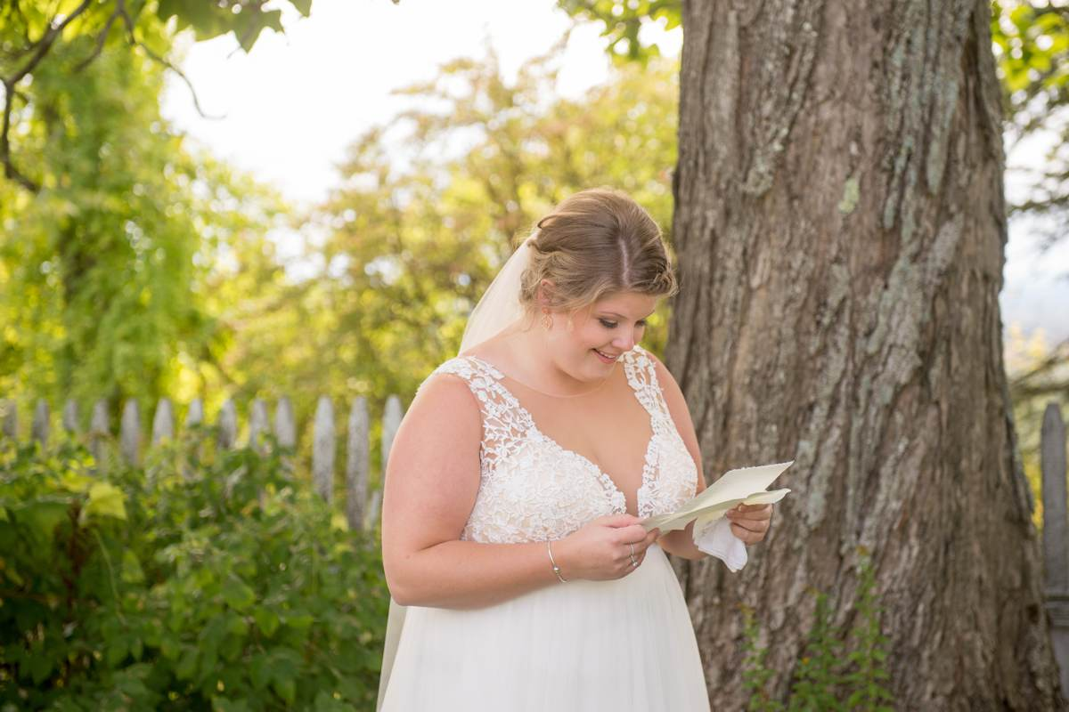 bride reading note on wedding day outside