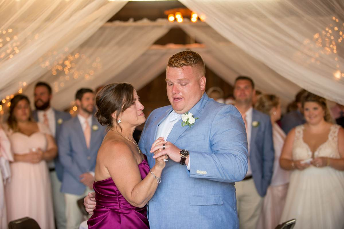 emotional groom dancing with mom in a barn reception